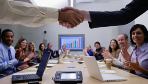 Business meeting at conference table - shaking hands