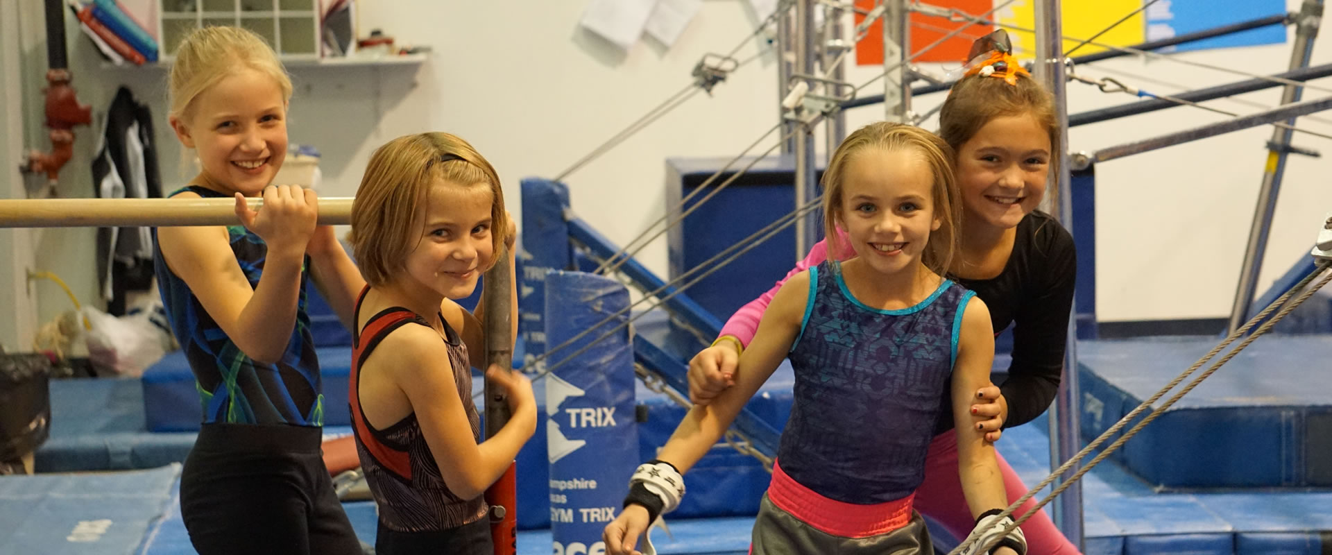 Young gymnasts smile for the camera during practice
