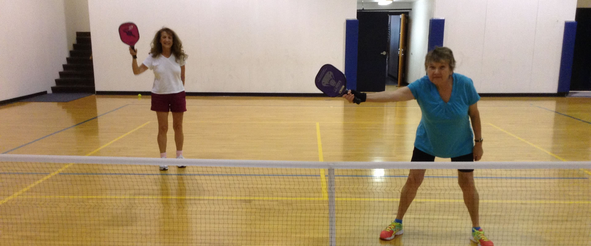 Two women waiting to receive serve while playing pickleball at Madison Turners