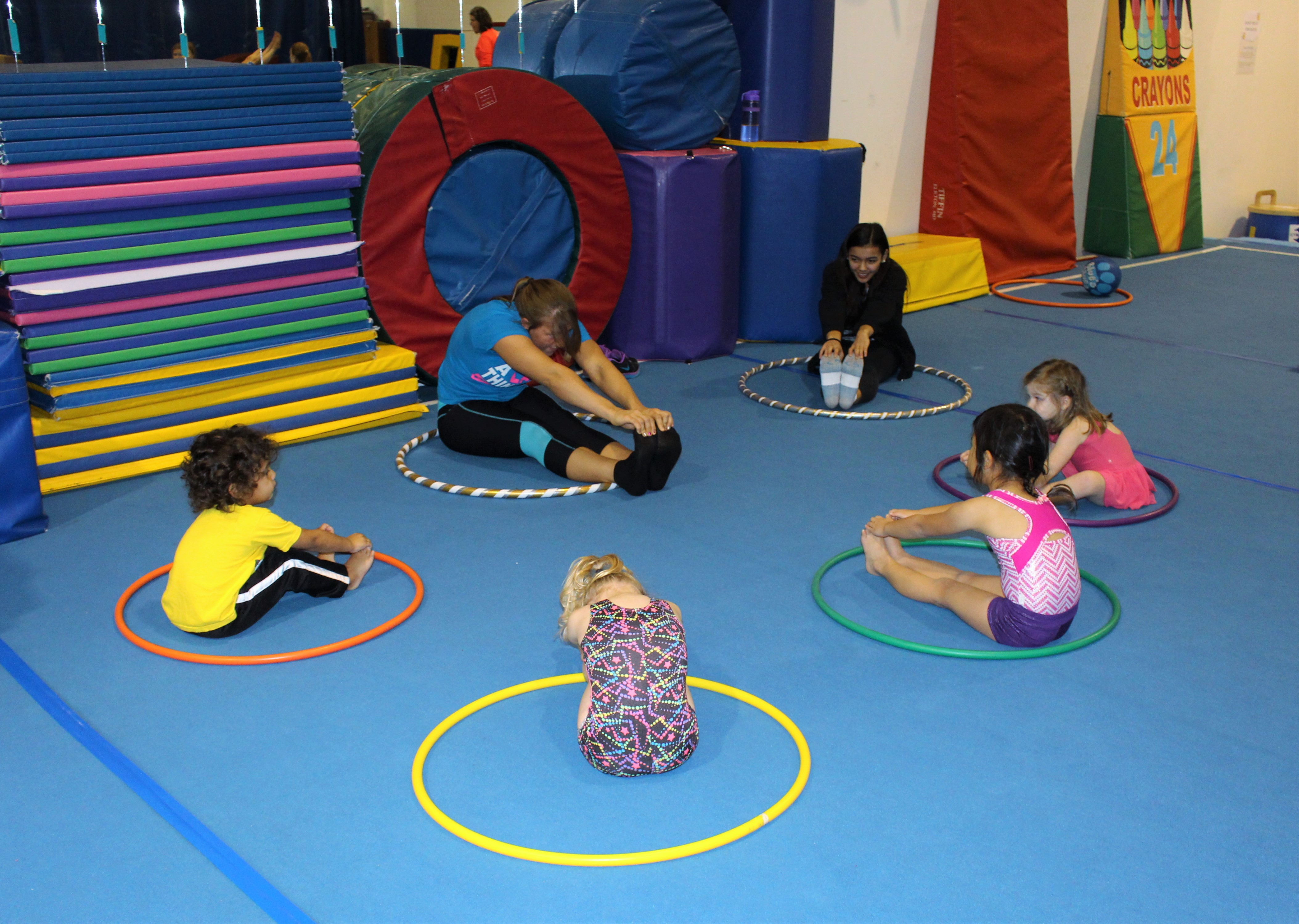 Picture of tots stretching while sitting in hula hoops